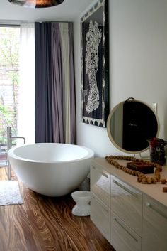 Interesting bathroom with timber floors, free standing bath, oversized art and curtains.