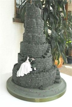 Six tiered wedding cake made in the style of a ruined castle with green vines and purple flowers. Also with a bride and groom sitting on the steps