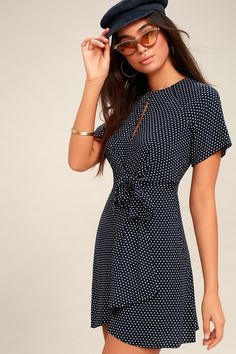 Entice your stylish sensibility with the Darling Details Navy Blue Polka Dot Knotted Wrap Dress! Light and breezy woven fabric, with a cute polka dot print, shapes short sleeves and a rounded neckline with keyhole accent. Tying front sash adds a trendy twist atop a wrapping mini skirt. Hidden back zipper/clasp.