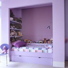 """Zamiast klasycznego, """"dziewczyńskiego"""" koloru różowego – delikatny liliowy. Poza zwracającym uwagę kolorem zastosowano tu proste rozwiązania. Zamiast stawiać łóżko przy ścianie i obok regał na zabawki, wymurowano wnękę i w niej urządzono kącik – tak, jak dzieci lubiąnajbardziej."""