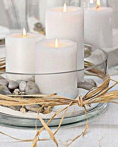 White candles on white sand with stones in a clear bowl. Cool coastal centerpiece.