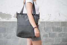A wonderful tote bag made of cotton canvas in gray color . It is designed with double straps so you can wear it as a shoulder bag but it also has a removable strap which you can adjust to your desirable length and wear it across the body.   ----It has 8 pockets in total! and it is specially designed to carry a laptop (15 laptop or less) in which we specially added extra padding for the best safety of the laptop or heavy books /magazines. It is a very roomy bag and it is double stitched so…