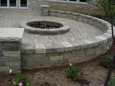 Stone patio with fire pit... I think I'd like it better without the wall.