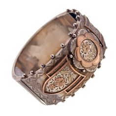 c.1890 sterling silver with rose gold fill cuff. Impressively wide and detailed, this antique bangle is delicately hand engraved with classic floral and scroll designs. The top perimeter of the cuff is castellated with 22 silver orbs for added detail.