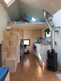 Interior design points of interest include a full-length opening window along the galley kitchen, a built-in reading cubby in the living area, and large storage stairs that climb over the refrigerator to the sleeping loft. Off Grid Tiny House, Tiny House Blog, Tiny House Community, Tiny House Living, Tiny House Plans, Tiny House On Wheels, House Floor Plans, Tiny Spaces, Small Apartments