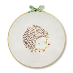 The Hedgehog Wall Art Embroidery Kit is a creative DIY hand embroidery kit from Penguin  Fish.  This is a fun embroidery project for beginners and experienced stitchers!  Kit includes cotton muslin fabric, 8-inch embroidery hoop, embroidery floss  needle, decorative ribbon, easy-to-trace pattern, iron-on transfer, stitch  color guide, and simple embroidery instructions.