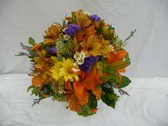 Orange alstroemeria, yellow daisy, queen anne's lace, orange lilies, camomile, caspia, purple statice and bupleurm