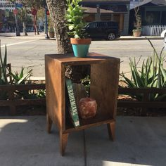 This is a super functional plant stand/end table. It is handmade by us in a mid century style. Looks classic with plants, but also great for books and knick knacks. This stands at 19 1/2 tall, 13 wide, 11 long/deep. PLANTS/BOOKS/CANDLES NOT INCLUDED.