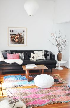 I normally shy away from black leather sofas (too 90s?) but this black leather sofa with white walls and colourful accents looks perfect.  The shape makes all the difference.