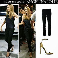 Angelina Jolie in black Saint Laurent pants, black top and gold open toe strap sandals