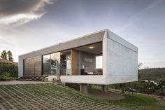 Un prisma de concreto se eleva sobre el terreno y resuelve el interior entre medio de una angosta crujía que revela las montañas en las afueras de Brasilia