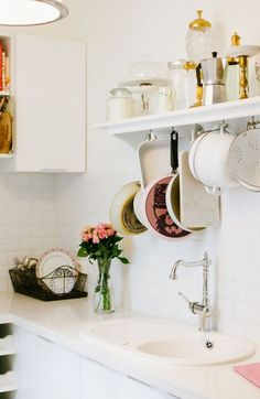 Open shelving in an all white vintage kitchen with hanging pots and pans and pastel pink roses.