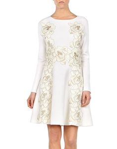 Holiday Season Looks - Blumarine Fall Winter 2015/2016 • Blumarine's white dress has a fitted bodice that flows gracefully to a feminine, flouncy hem. This forgiving stretch-knit design is adorned with macramé lace flowers, strategically placed for a flattering slimming effect. Work yours with a tonal clutch and red shoes.