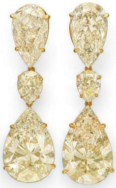 Colored diamond earrings. Each suspending a pear-shaped fancy light brownish yellow diamond or light yellow diamond, weighing approximately 10.07 and 10.06 carats, from an inverted pear-shaped light yellow diamond link, weighing approximately 5.03 and 5.05 carats, to the inverted pear-shaped light yellow diamond surmount, weighing approximately 1.17 and 1.01 carats, mounted in 18k gold, via Christie's.