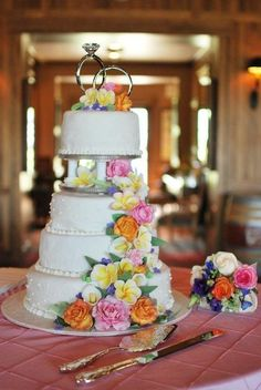 """Daughter's wedding cake - Four tierd fondant covered wedding cake. Royal icing borders with dots on 8"""" and 12"""" cake. 6"""" and 10"""" cake have design mat design. Hand-painted flowers are gumpaste circus roses,  pink roses, calla lillies, and plumerias. Leaves and mums added for filler."""
