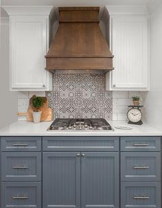 FS Faenza black and white tile backsplash. White subway tile, walnut stained wood kitchen vent hood. White Reflections quartz countertop.