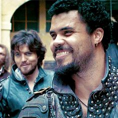 Athos in the background: He never laughs, but he sure can smirk.