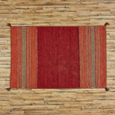 Fogarty Area Rug, Red | A creative blend of textures, this southwestern-inspired rug adds artful intrigue to any space with its strips of pattern and braided trim.