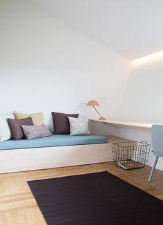 Plassbygd sofa som også kan benyttes som gjesteseng. Arbeidsbordet strekker seg fra vegg til vegg.