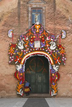 ~Decorated Church door Mexico........ A Purepecha woman leaves the church of Pichataro Michoacan after paying her respects to the Virgen Mary on the Feast of the Assumption.......via Flickr - Photo Sharing!