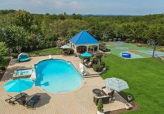 This Centreville, Virginia, backyard offers fun for all with a gorgeous pool and spa surrounded by brick pavers, a pool house with an outdoor bar and half bath, sport court, sound system and amazing mountain views.