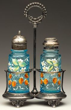 "HONEYCOMB PILLAR PAIR OF SALT AND PEPPER SHAKERS, turquoise with polychrome floral, strawberry and dragonfly decoration, each with near-matching period two-part lids. Fitted in a quadruple-plate stand marked ""TO.B.P.COMPANY"". Possibly Mt. Washington Glass Co. Fourth quarter 19th century"