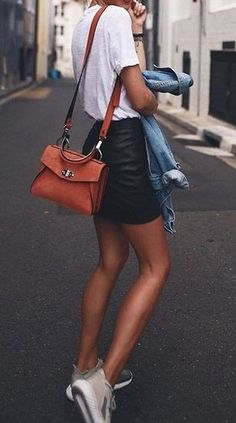 black + white outfit. leather mini skirt. plain tee. tan bag. sneakers. denim jacket. street style.