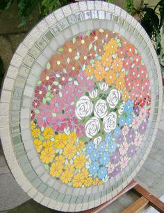 Tampo em moisaico com moitvo floral em placa cimenticia medindo 70 cm de diametro