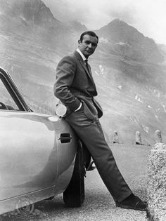 "Sean Connery posing by this 1964 Aston Martin in Switzerland for the James Bond movie ""Goldfinger"". Sean Connery and the 007 franchise would achieve world-renowned status and never look back. Sean Connery James Bond, Aston Martin Db5, Style James Bond, Jaguar E Typ, Bond Cars, Photo D Art, Cool Costumes, Akita, Black And White"