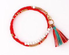 This listing is for one single strand wrap multicolored bracelet in cream, coral, peach, light purple, turquoise, mint green, chocolate and gold with oval 22K gold plated bead & two dark green tassels.  Details: - 22K matte oval gold plated oval bead, - mix of seed beads, - gold plated brass beads & metal findings, - cotton tassels, - approx. 14.75 L (designed to fit 7-7.25 wrist)  All Felt Like Paper items arrive in muslin bag(s). If your order is a gift please specify if you would l...
