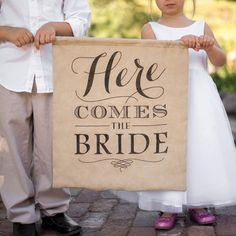 """The flower girl and ring bearer holding a rustic """"Here Comes the Bride"""" sign, super cute!"""