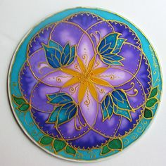 The purple flower ( the Seed of Life) Is the element from which all things come from spiritual wisdom and insight. The yellow center is the personal power we have. The 4 butterflies represent transformation into physical form and the green leaves are creating through the heart. This mandala is hand painted on a 10 inch silk covered hoop.