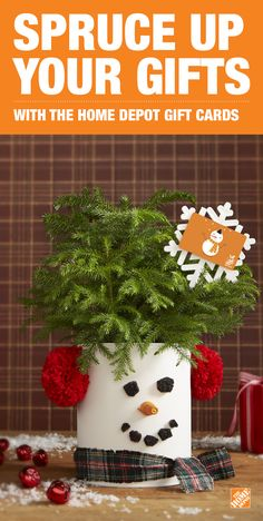 """Get creative this holiday season The Home Depot gift cards and this adorable DIY Snowman Bucket. • Prime and paint the outside of the metal gallon paint can. • Next, paint a coarse grit metal finishing pad with black paint. • Cut the dried finishing pad into """"coal"""" eyes and mouth, then attach with a hot glue gun. • For the nose, hot glue an orange wire connector. • Glue pom poms to create ear muffs, then tie a ribbon to make a scarf. • Finish with a seasonal plant and a gift card!"""