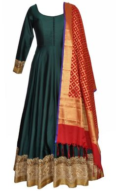 This set features a bottle green floor length suit in silk base with a beautiful blend of gold zari and thread embellished border. It also features a sheer back with matching dori tie up with gold tasseled hangings. The contrast banarasi dupatta enhances the beauty of the outfit. It is paired with a matching churidar pants. Fit into this extremely trending and in-vogue creation for an elegant look. Note: The design of the banarasi dupatta may change based on availability but the colour…