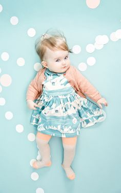 Adorable outfit & little girl. However, I think that I could see more of the details of the dress if the background was a different color.
