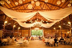 Round paper lanterns and white draped ceiling fabric hang in a barn venue for a rustic wedding reception. Barn Wedding Dress, Rustic Wedding Reception, Reception Party, Barn Wedding Venue, Farm Wedding, Dream Wedding, Rustic Weddings, Country Weddings, Reception Ideas