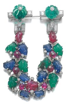 An Art Deco gem set and diamond brooch, 'Tutti Frutti', Cartier, 1929. Of garland design, set with carved rubies, emeralds and sapphires, single-cut and baguette diamonds, signed Cartier, numbered. (=)