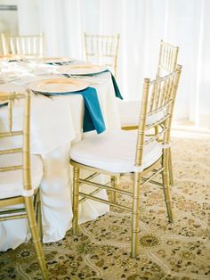 Gold chiavari chairs with blue napkin accents give off a sophisticated feel! Photographer: Honey Honey Photography