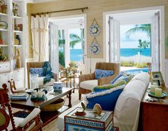 """This living area opens to a view of the Gulf of Mexico. Canvas draperies with starfish tassels and rope tiebacks allude to the home's nautical theme. """"I wanted to give the room the feel of a sea captain's cottage,"""" says designer Phyllis Taylor."""