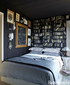 """In Stephen Shubel's """"moody and eclectic"""" bedroom in his California house, he mounted flea-market finds against a black wall. Genuine Fake Books wallpaper by Deborah Bowness creates the illusion of more space. Comforter and striped pillowcases, West Elm."""
