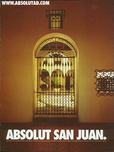 ABSOLUT SAN JUAN is an ad on page 1 of Bienvenidos 1999, the Official Visitors Guide of the Puerto Rico Hotel & Tourism Association. This new 1998 ad features a window inside a room in a brown wall, looking out onto a beautiful view of an internal, Spanish style courtyard as might be found in the city of San Juan, Puerto Rico, or in the Old San Juan section of that city.