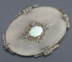 "Theodor Fahrner matte rock crystal brooch of silver with marcasites, and an opal cabochon, oval quatrefoil design, ca. 1928. Marked ORIGINAL FAHRNER and sterling mark. 1 1/2"" x 2""."