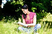 A young woman sitting cross-legged on the grass, reading a magazine - Stock Photo