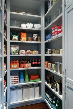 Lovely walk-in pantry features floor to ceiling built in shelving painted gray.