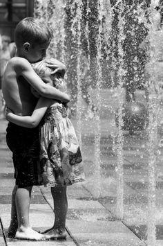 Hermanos abrazados mojándose en una fuente