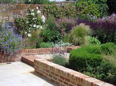 brick garden walls, perennial border, bronze fountain