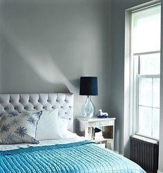 light blue bedspread, gray walls, bedroom. upholstered headboard.