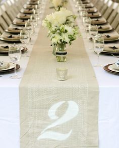 """At Wendy and Ben's wedding, the table runners were screenprinted by Satisfactory with a pattern that mimicked rows of stitching. The pattern, inspired by Indian """"gudari"""" quilts, extended over the ends of each table, where large numbers were stenciled."""