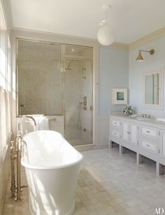 An airy and bright guest bathroom featuring a free-standing tub | archdigest.com guest bath.