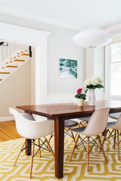 """In the dining room Jessica changed the paint color, <a href=""""https://www.polyandbark.com/eames-style-molded-plastic-dowel-leg-side-chair-dsw-walnut-legs-set-of-2.html"""" target=""""_blank"""">chairs</a>, rug, and art. Like the living room, the space had all of the right bones but needed some cohesive decorative accents."""